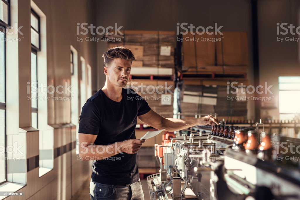 Brewer examining the beer production in brewery plant stock photo
