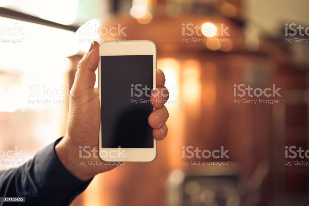 Brewer holding a smart phone in microbrewery Close up of master brewer holding a smart phone with blank screen in microbrewery Adult Stock Photo