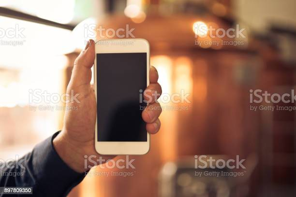 Brewer Holding A Smart Phone In Microbrewery Stock Photo - Download Image Now