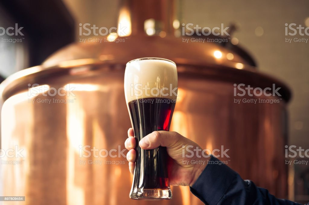 Brewer holding glass of bitter ale beer at brewery Close up of male brewer holding glass of bitter ale beer in front of copper vat Adult Stock Photo