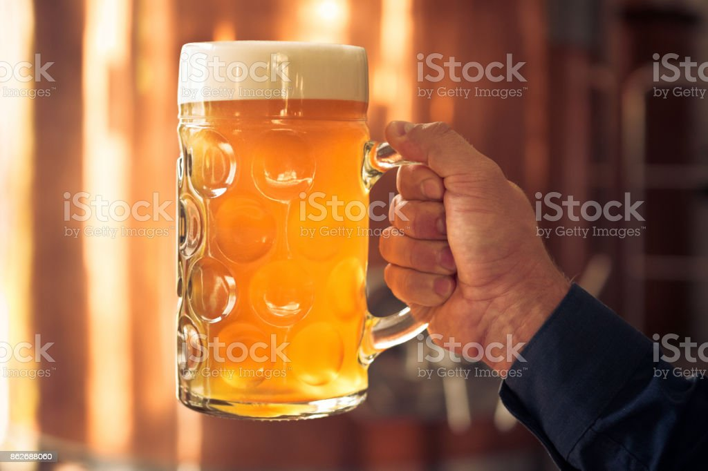 Brewer holding mug of beer in front of copper vat Man holding mug of beer in the microbrewery. Close up of mug and hand, unrecognizable people. Copper vat in the background. Adult Stock Photo