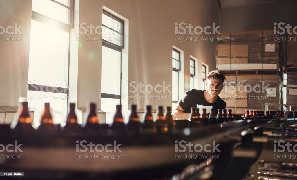 Brewer looking at conveyor with beer bottles stock photo