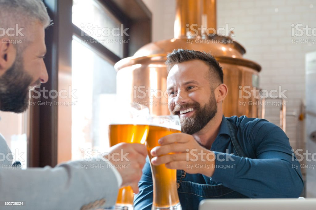 Brewer master toasting with beer glass with his friend Brewer master toasting with beer glass with his friend. Copper vat in the background. Adult Stock Photo