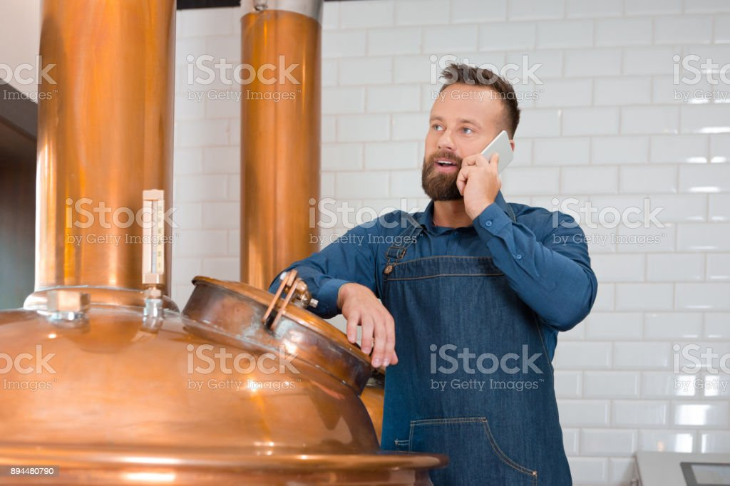 Brewer talking on phone in microbrewery Mature man talking on mobile phone in fermenting section of beer manufacturing factory. Master brewer talking on phone in his microbrewery Adult Stock Photo