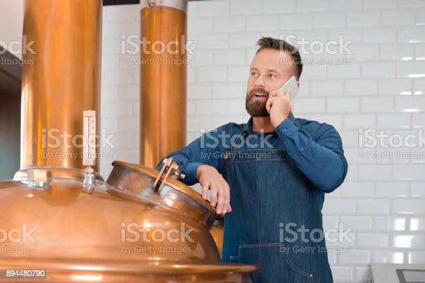 Brewer Talking On Phone In Microbrewery Stock Photo - Download Image Now