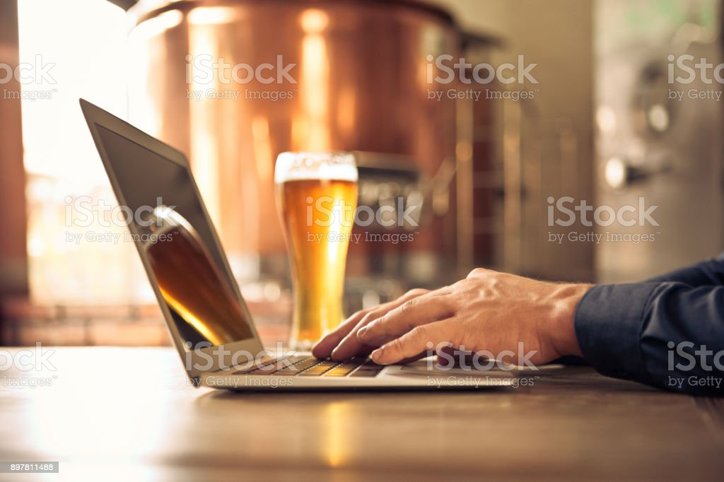 Brewer using laptop at micro brewery Close up of master brewer hands using laptop computer at micro brewery. Man sitting at table with laptop and beer glass. Adult Stock Photo