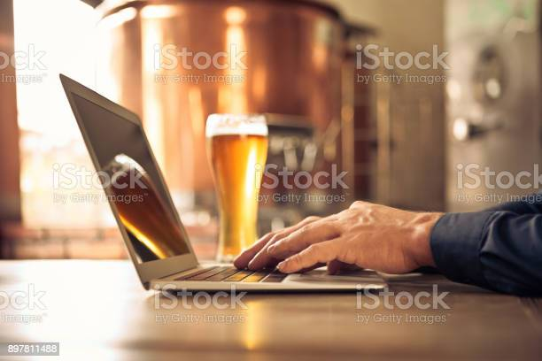 Brewer Using Laptop At Micro Brewery Stock Photo - Download Image Now