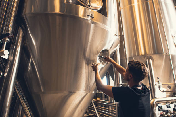 brewer working with industrial equipment at the brewery - brewery tanks stock pictures, royalty-free photos & images