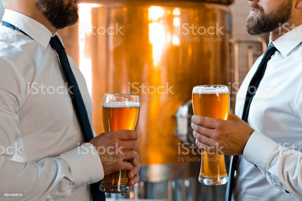 Brewery business partners talking over beer Mid section shot of two businessmen with beer pint glasses talking in micro brewery. Cropped image of brewery business partners talking with a glass of beer. Adult Stock Photo