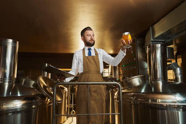 맥주를 검사하는 양조장 전문가, 유리를 들고. - 맥주 공장 뉴스 사진 이미지