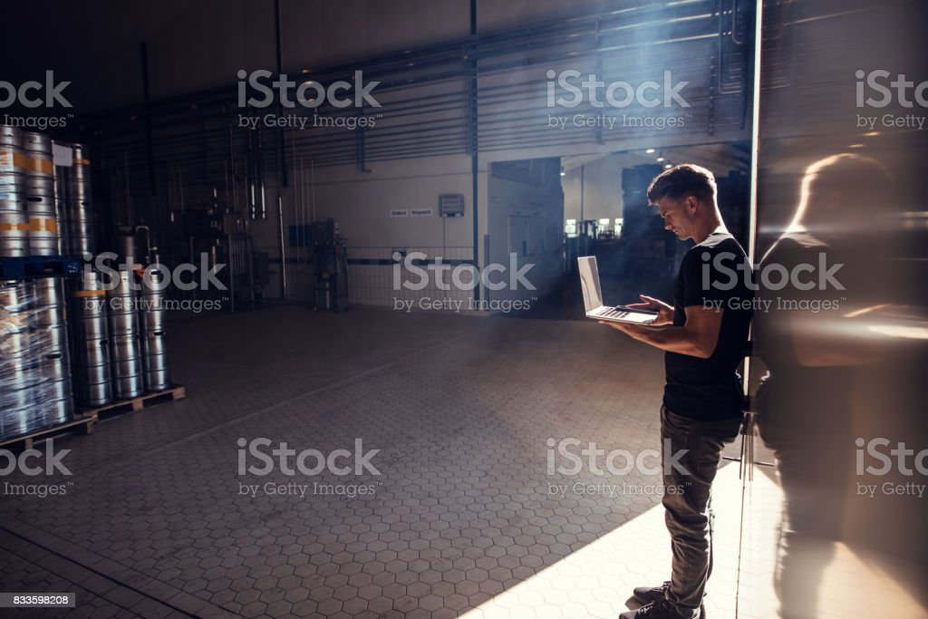 Brewery factory owner using laptop stock photo