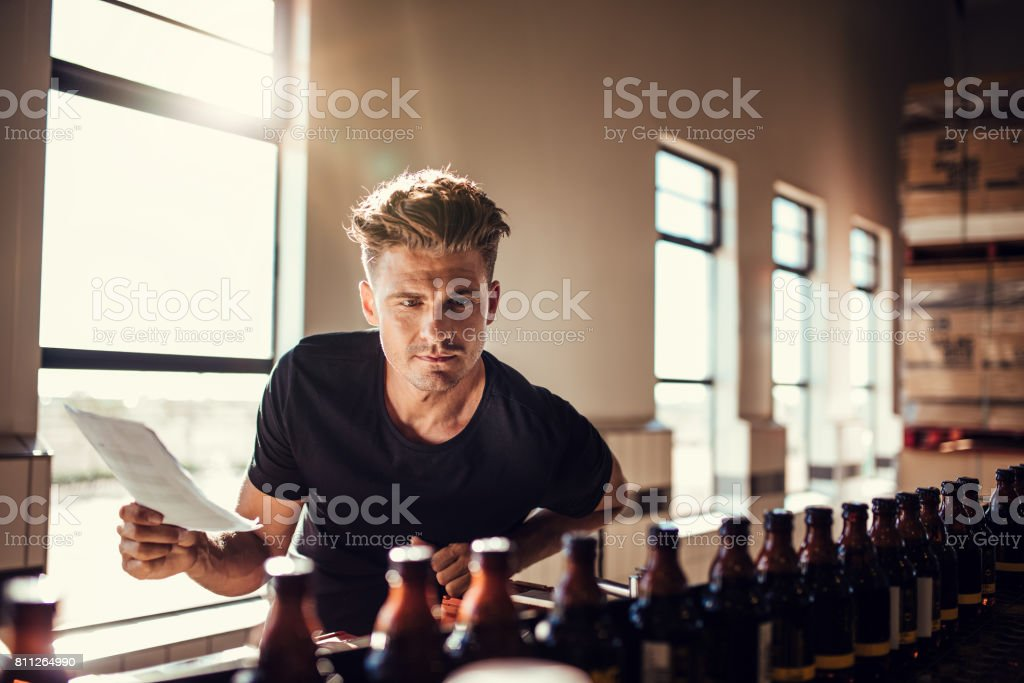 Brewery factory worker examining the quality of craft beer stock photo