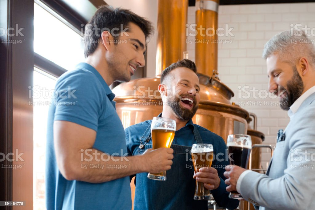 Brewery team having beer after work Microbrewery team having beer after work. Three man drinking beers and smiling at brewery. Adult Stock Photo
