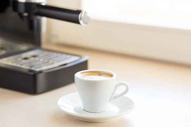Brewing classic espresso with coffee machine Brewing classic espresso with coffee machine. Coffee with brown froth in small white cup on the kitchen table near window sergionicr stock pictures, royalty-free photos & images