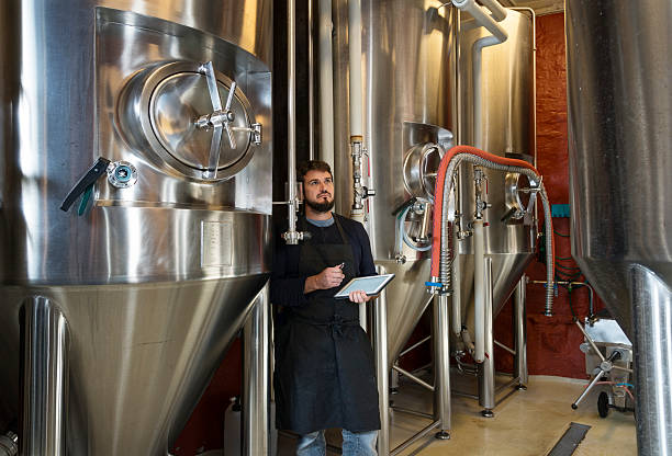 brewmaster checking his brew - brewery tanks stock pictures, royalty-free photos & images