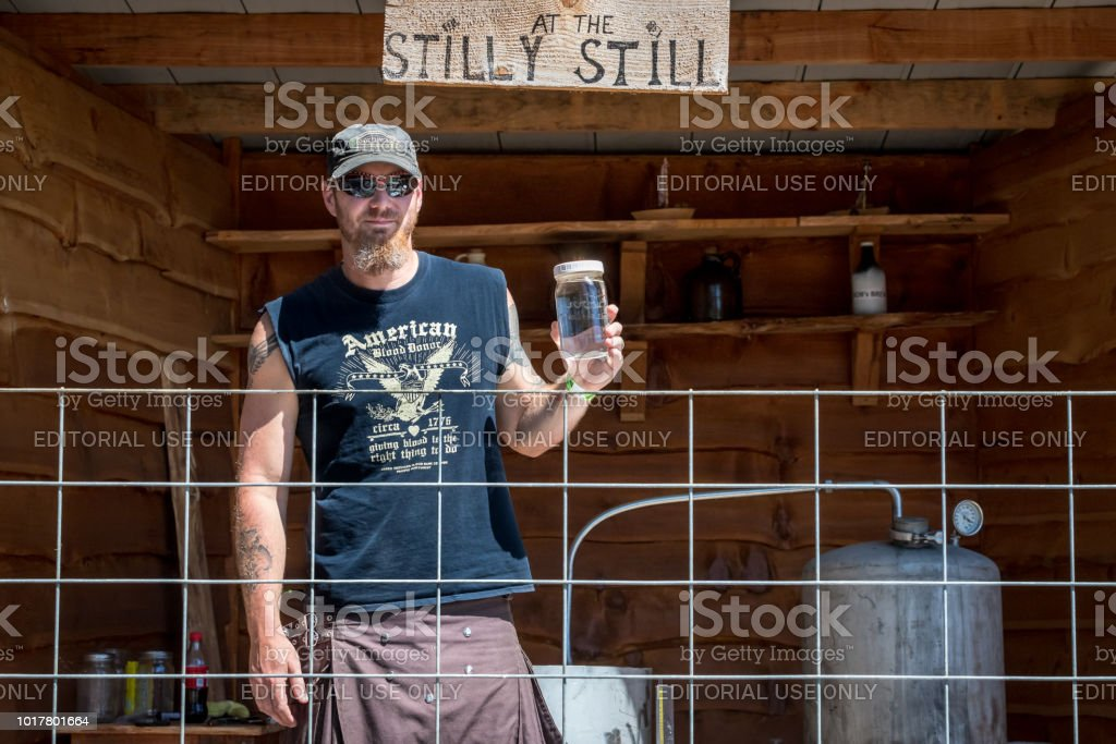 Brewmaster showing how clear rum alcohol is from his still during a moonshine demonstration stock photo