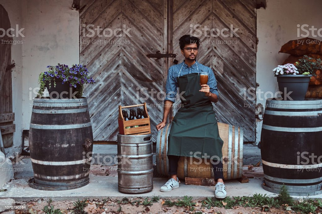 Brewmaster sitting on a wooden barrel and holds a glass of craft beer, relaxes after work. stock photo