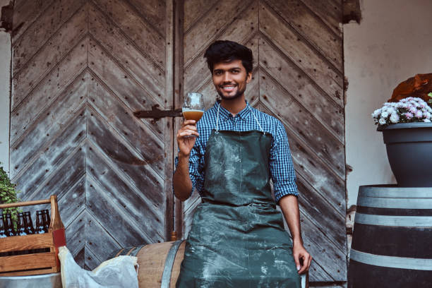 Brewmaster sitting on wooden barrel and holds a glass of craft beer relaxes after work. stock photo