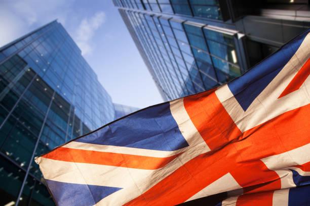 brexit concept - britse economie na brexit deal - dubbele blootstelling van vlag en canary wharf business center wolkenkrabbers - britse cultuur stockfoto's en -beelden