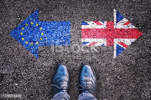 istock Brexit, flags of the United Kingdom and the European Union on asphalt road with legs 1175213416