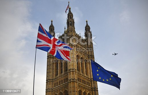 Protesters flags of United Kingdom and European Union outside Parliament in Westminster during the Brexit debates. A British Airways flight passes overhead