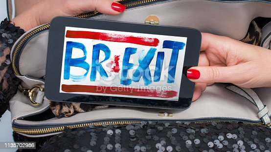 Mature woman takes tablet of EU Brexit out of her purse Image on tablet by contributor and available on istock
