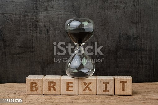 istock Brexit, time countdown for the UK to deal and withdraw from Euro zone concept, sandglass or hourglass on wooden cube block with alphabet building the word BREXIT on wood table, dark black background 1161941760