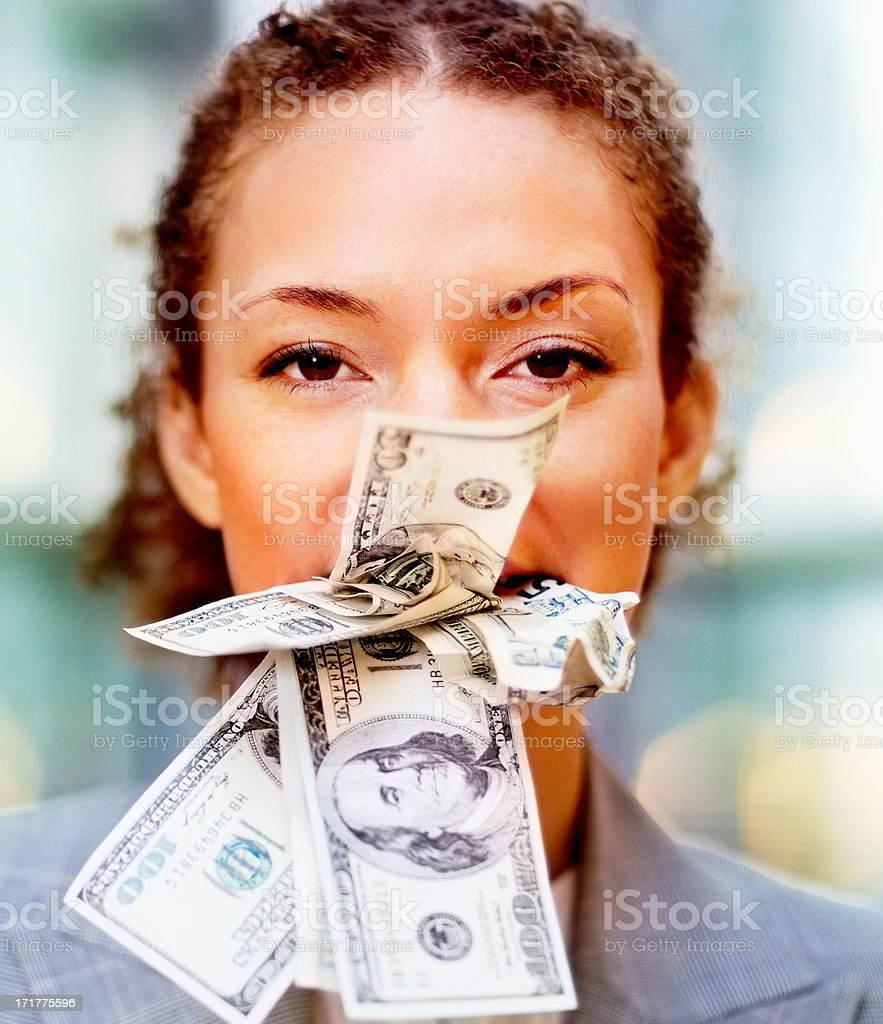 Bribe: Business woman with money stuffed in her mouth stock photo