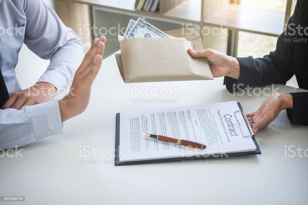 Bribery and corruption concept, Businessman refusing receive money in the envelope to agreement contract, A bribe in the form of dollar bills stock photo