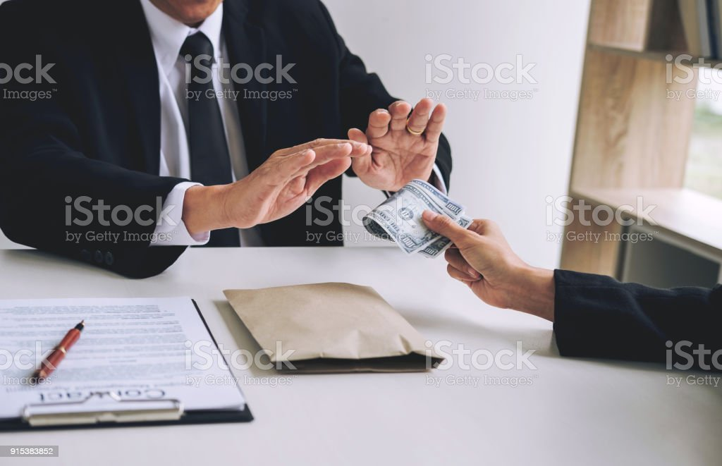 Bribery and corruption concept, senior businessman manager refusing receive money in the envelope to agreement contract, A bribe in the form of dollar bills stock photo