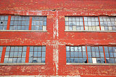 Rows of broken glass windows on a brick wall of a run down factory in run down area of Detroit, MI