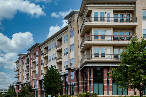 Modern brick and stucco condo buildings with balconies and garages