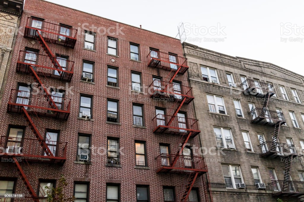 Brick apartment condo building exterior architecture in Fordham Heights center, Bronx, NYC, Manhattan, New York City with fire escapes, windows, ac units in evening stock photo