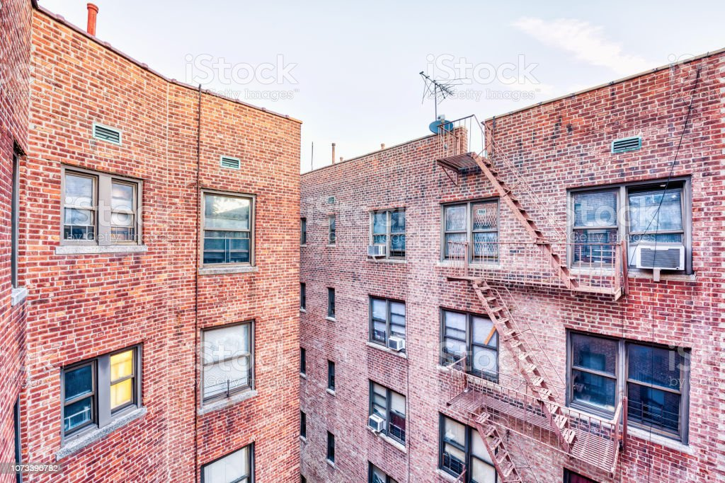 Brick apartment condo building roof exterior architecture in Fordham Heights center, Bronx, NYC, Manhattan, New York City with fire escapes, windows, ac units in morning, satellite dish, antenna, USA stock photo