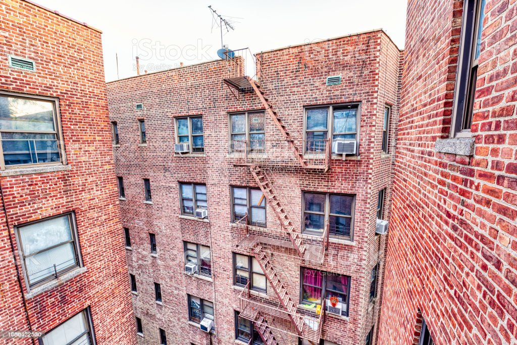 Brick apartment condo building roof exterior architecture in Fordham Heights center, Bronx, NYC, Manhattan, New York City with fire escapes, windows, ac units in morning, satellite dish, antenna stock photo