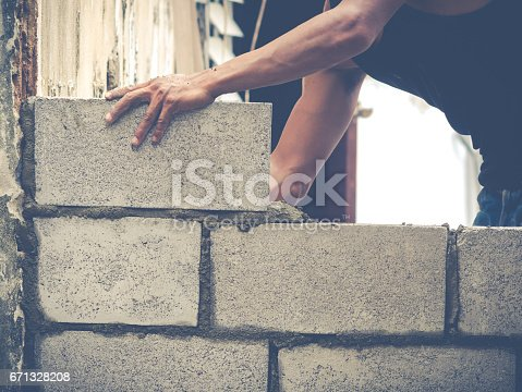 istock Brick Builders Are Building Walls 671328208