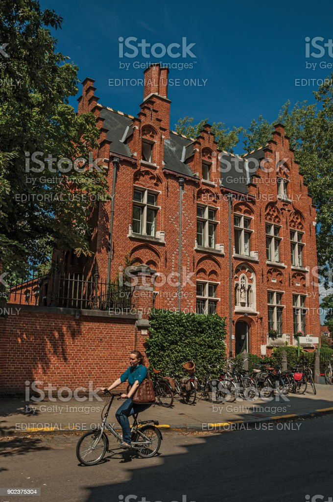 Brick building and woman riding a bicycle in Bruges. stock photo