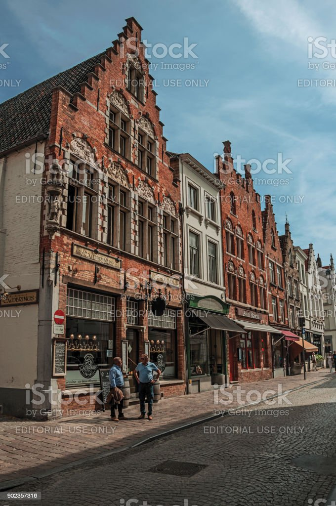 Brick building, shops and people in street of Bruges. stock photo