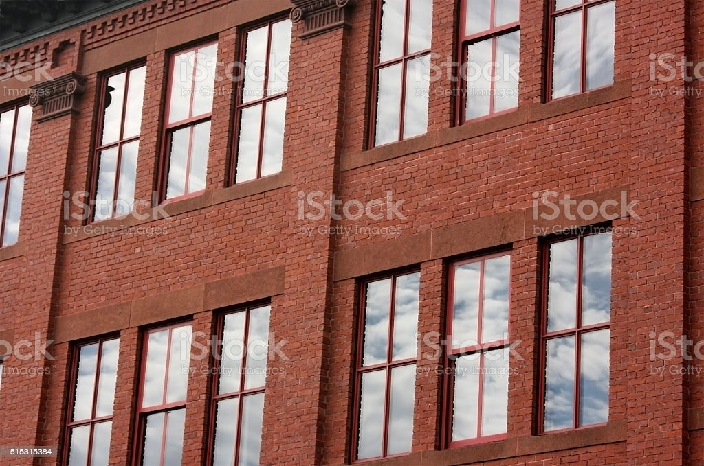Brick building with windows reflecting clouds and sky stock photo