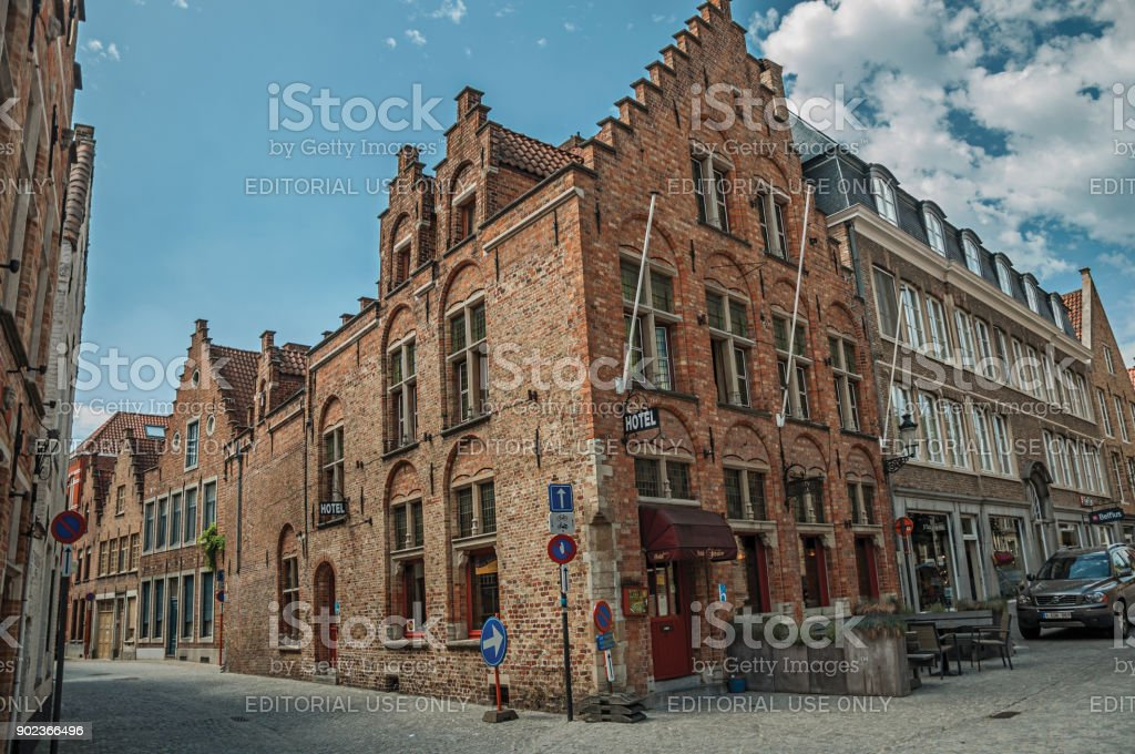 Brick buildings in empty street and blue sky at Bruges. stock photo