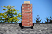 Part of tiled roof with brick chimney against blue sky with beautiful cloud formations and diagonal composition