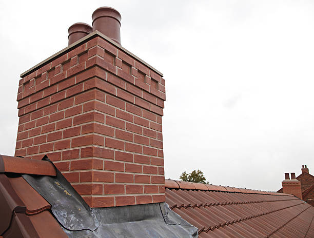 Brick chimney with two chutes sitting atop shingled roof stock photo