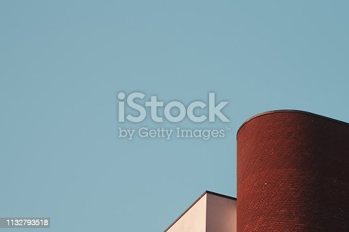 Brick clad and rendered architectural elements on the roof line of an office building, against a clear blue sky.  Belfast, Northern Ireland.