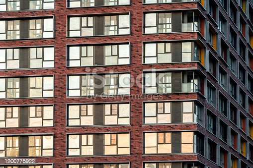178842131 istock photo Brick facade of a residential multi-storey building with large windows. Modern architecture. Real estate in a big city. Background from the wall of the house. 1200775922