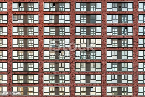 178842131 istock photo Brick facade of a residential multi-storey building with large windows. Modern architecture. Real estate in a big city. Background from the wall of the house. 1200776640
