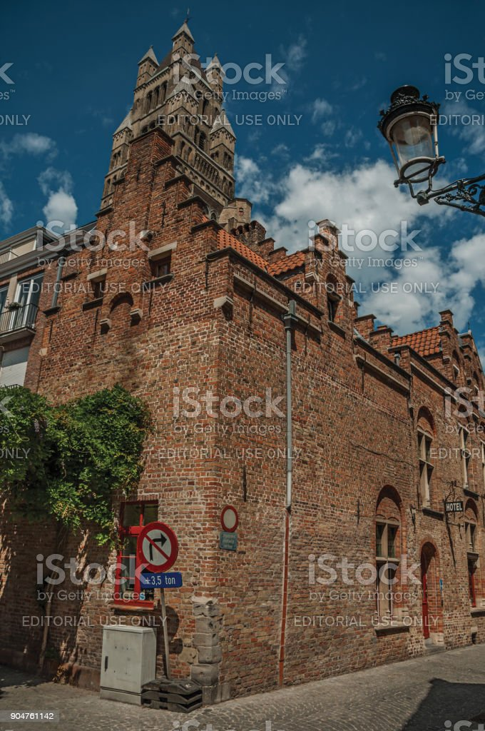 Brick facade of an old building and tower, on a street corner of Bruges. stock photo