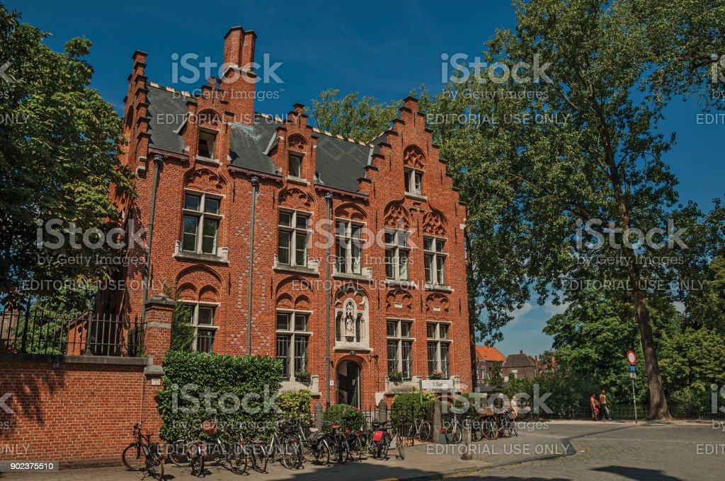 Brick facade of old house, trees and bicycles in Bruges. stock photo
