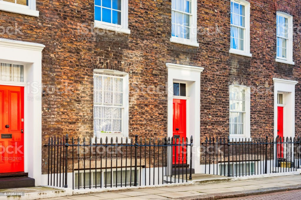 Brick Facade Row Houses With Red Front Doors In London England Uk