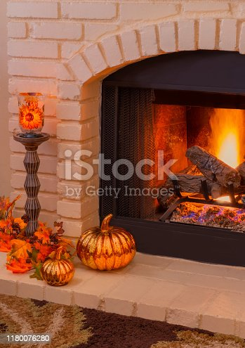 istock Brick fireplace with fall decorations and burning logs (P) 1180076280