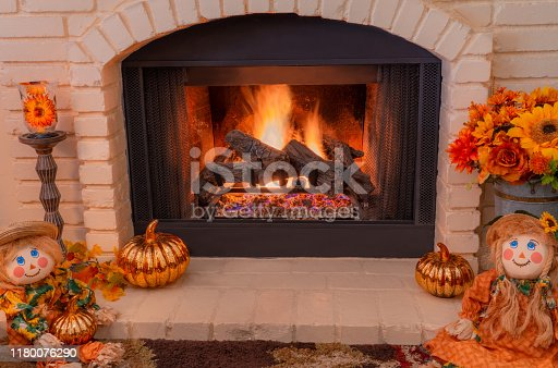 A cozy old fashioned brick fireplace burns and is surrounded by fall decorations and pumpkins. Flowers and glass pumpkins and two scarecrow dolls  sit on the hearth.  metal vase, glass pumpkin, burning fireplace, burning embers, ragdolls, hearth